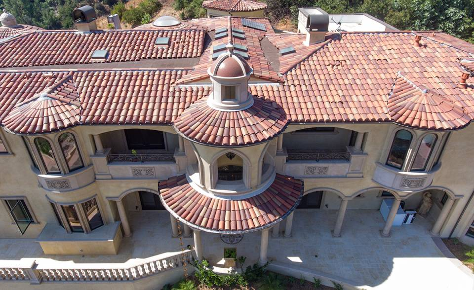 View of front turrets and roof on custom mansion on a hilltop in Bradbury California featuring Classic Tapered two piece terra-cotta clay roof tile with turrets, domes, and dome awnings in custom color blend CB477.