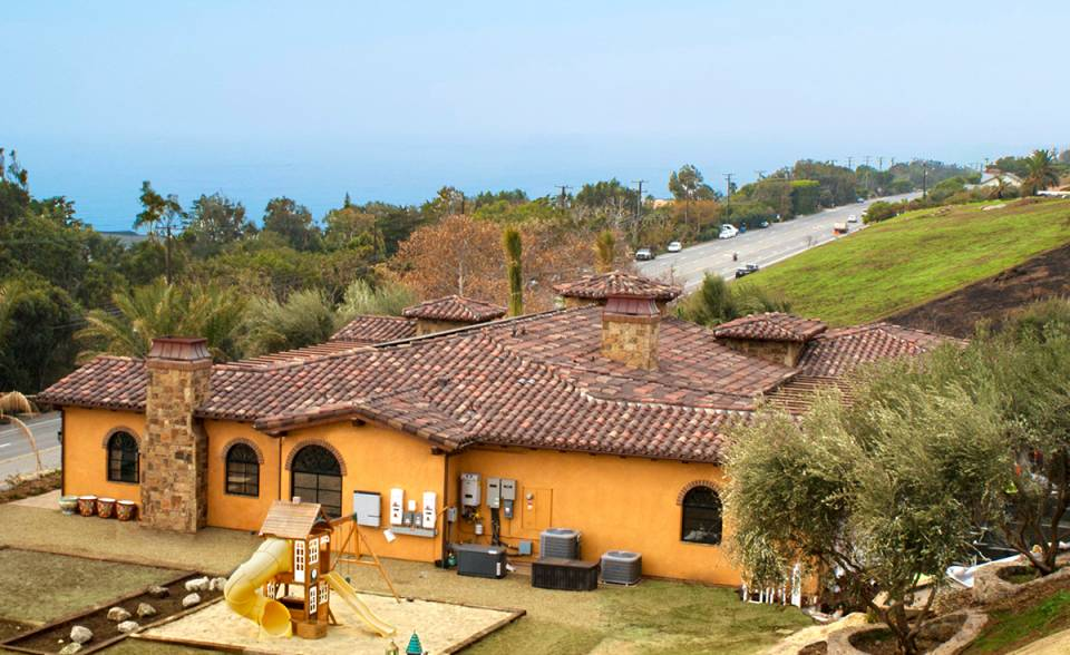 Hilltop view of Corona Tapered mission two piece clay roof tile in custom blend 50% 2F45CC16D, 20% B317-R Taupe Smoke Blend, 20% 2F45 Tobacco, 10% B330-R Santa Barbara Blend with 100% 2F45 pans and boosters to match tops on gorgeous one story house in Malibu California