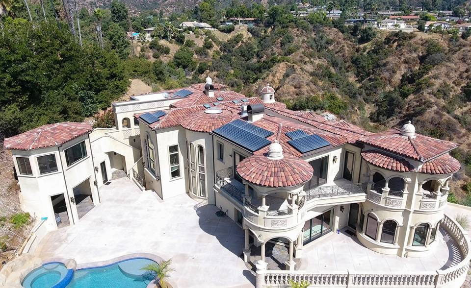 Full overhead view of back of a custom mansion on a hilltop in Bradbury California featuring Classic Tapered two piece terra-cotta clay roof tile with turrets, domes, and dome awnings in custom color blend CB477.