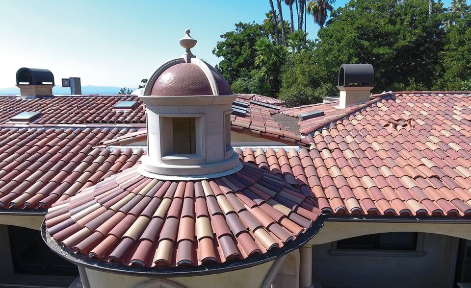 Close up view of front turret and roof on custom mansion on a hilltop in Bradbury California featuring Classic Tapered two piece terra-cotta clay roof tile with turrets, domes, and dome awnings in custom color blend CB477.